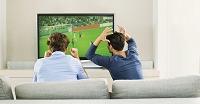 ソファでサッカーの試合をテレビ観戦する
