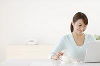 お茶を飲みながらパソコンをする若い日本人女性