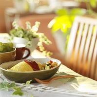 テーブルの上のオムライスと観葉植物