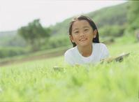 草原でうつぶせになる女の子