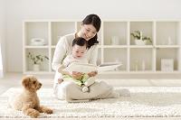 リビングでお母さんに抱っこされて絵本を読む赤ちゃん