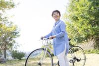 自転車を押して散歩するシニア日本人女性