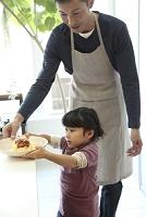 父親を手伝ってパスタ皿を運ぼうとする幼い女の子