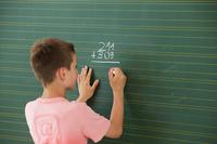黒板で足し算をする男の子