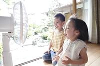 縁側で扇風機にて涼む2人の子供