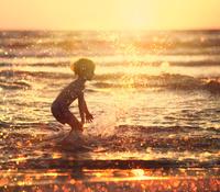 夕日に輝く夏の海で遊ぶ子供