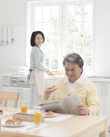 朝食の準備をする妻と新聞を読む夫