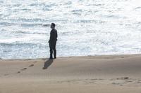 波打ち際に立つ日本人ビジネスマン