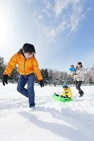 雪の公園でソリを引いて歩く親子