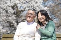 ベンチに座り桜を眺めるシニア夫婦