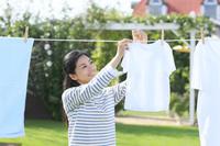 広い庭で洗濯物を干す日本人女性