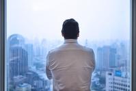 窓辺から遠くを見るビジネスマン