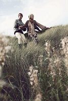 丘を歩く若いカップル