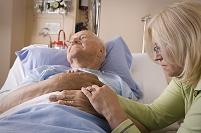 ベッドに横たわるシニアの手をとる女性