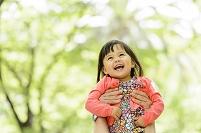 新緑の公園で高い高いして喜ぶ女の子