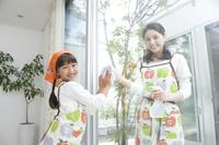 窓拭きをする母と娘