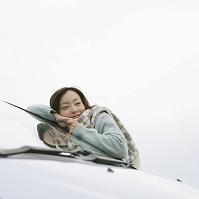 車にもたれかかる日本人女性