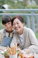 テラスで食事する孫と祖母