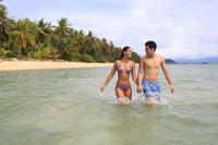 海に入る若いカップル