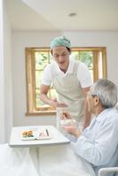 食事を手伝う介護士男性とシニア男性