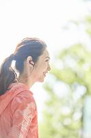 音楽を聴くランニングウェアの日本人女性
