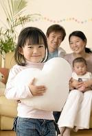 ハートのクッションを抱く女の子と日本人家族