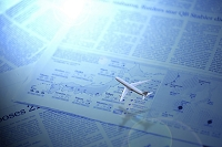 宙に浮いたミニチュアの飛行機と英字新聞