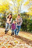 秋の公園で遊ぶ日本人家族