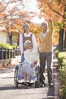 車椅子のシニア夫婦と介護ヘルパー
