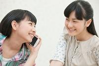 スマートフォンで通話する女の子と友達
