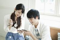 スマートフォンを使う20代の若いカップル