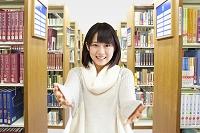 本棚の前で手を広げる女性