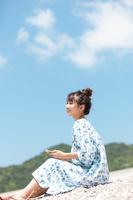 砂浜に座ってスマホを持っている日本人女性