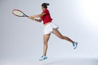 バックハンドをするテニスプレーヤー