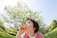 公園でシャボン玉を吹く女の子