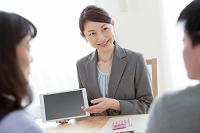 タブレットを見せて説明をする日本人ビジネスウーマン