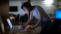 オフィスでパソコンを見る残業中の女性
