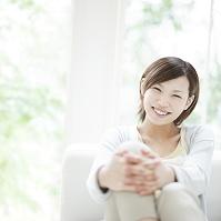 窓辺で膝を抱えて座る笑顔の日本人女性