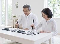 習字を書くシニア夫婦