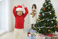 クリスマスツリーの前で喜ぶ女の子と犬を抱いたお母さん