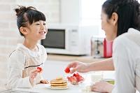 イチゴを持つ女の子と母親