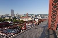 アメリカ 自転車で橋を渡る男性