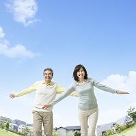 手を広げて立つ中高年夫婦