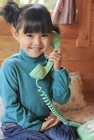 ログハウスで電話をかける女の子