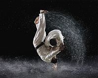 水しぶきをあげながら投げる柔道選手