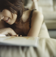 ソファで雑誌を見る日本人女性