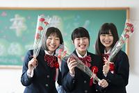 花を持ち微笑む女子学生