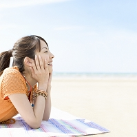 海辺で頬杖をつく日本人女性