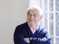 窓辺で腕を組むシニアの日本人男性
