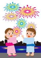 家並みと花火を見る女の子と男の子